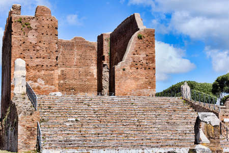The Capitolium at archaeological excavations of Ostia Antica surrounded by ruins, columns and remains of statues and bas-reliefs