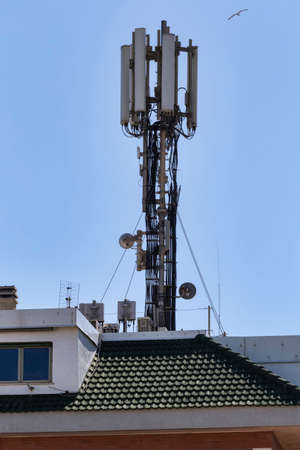 Telecommunication tower positioned on the roof of a building Stock Photo