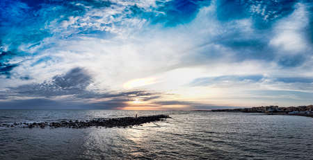 Panoramic pastel-colored sunset on the coast of Rome, with awesome sky , the calm sea and a relaxing atmosphere 스톡 콘텐츠