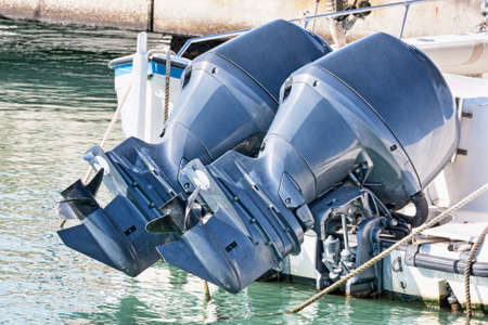 Couple of used blue outboard engines mounted on a speedboat Archivio Fotografico - 129623302