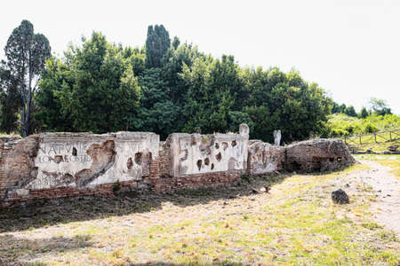 Roman Archaeological excavations of Ostia Antica with fragments of ancient latin inscriptions placed on the attic of Porta Romana - Rome Archivio Fotografico - 129623308