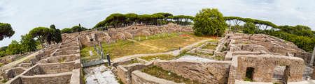 Panoramic view - 180 degree in the excavation ruin at Ancient Ostia - from the Decumanus Maximum to the Neptune thermal baths with the view of the republican ware of the spa - Rome Archivio Fotografico - 129623315