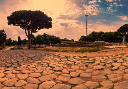 Beautiful and immersive scenic landscape at  sunset in Square of Victory located at  the archeological excavation at Ostia Antica with the cobblestones of decumanus maximum , a large nymphaeum, the Roman door and the famous sculpture of the winged Minerva-Victoria - Rome, Italy Archivio Fotografico - 129623359