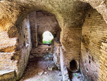 Corridor with Roman vault inside an ancient building in the archaeological excavations of Ostia Antica in Rome, Italy Archivio Fotografico - 129623377