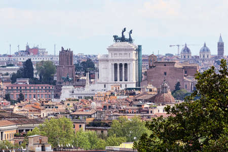 A look to Rome and its urban architectural beauties with the profile of the monumental altar of the homeland, historic buildings and ancient houses and many domes of churches Archivio Fotografico - 129623379