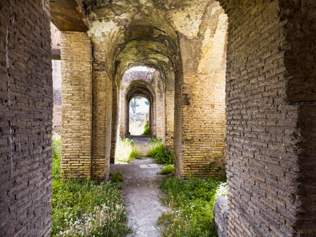 Corridors of the ancient Roman buildings in the archaeological excavations of Ostia Antica, arches and ceilings with stuccoes and well preserved decorations, Rome Italy