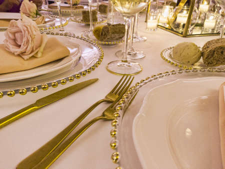 Festively decorated wedding table with tablecloth and rose flowers and golden cutlery to celebrate the party Archivio Fotografico - 129623405