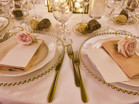Festively decorated wedding table with tablecloth and rose flowers and golden cutlery to celebrate the party Archivio Fotografico - 129623406