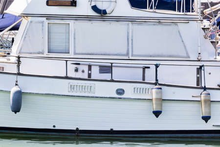 White wooden motor boat profile with fenders and roller blind Фото со стока