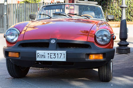 Rome,Italy - July 21, 2019: Rome capital city Rally event, an exhibition of vintage cars with beautiful British sport cabriolet car model MG in red color.