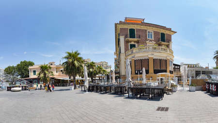 Ostia Lido Rome, Italy - July 19, 2019: Immersive panoramic street view of Lucio Coilio road ,with a beautiful liberty style palace and commercial business waiting for customers in a quiet sunny day Archivio Fotografico - 129584241