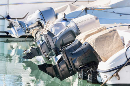 A row of outboard nautical engines mounted on fiberglass boats