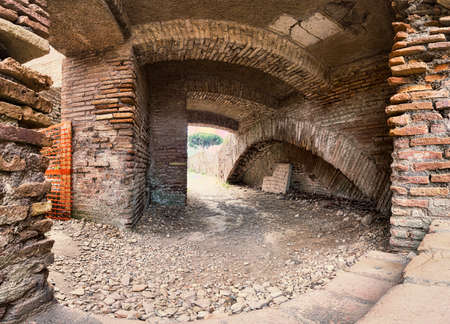 Archaeological excavations street view of ancient Roman ruin with vaults and pathways surrounded by brick walls