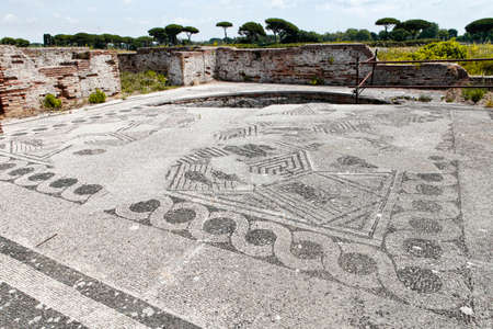 View of the eastern environment of the ancient Roman ruins of Porta Marina's thermal baths, with beautiful paving mosaic Archivio Fotografico - 129623441