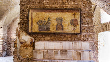 Roman empire archaeological excavations in Ostia Antica with the interior of the Termopolio s tenement and the marble shelf surmounted with decorative still life frescoes.  Rome , Italy Фото со стока