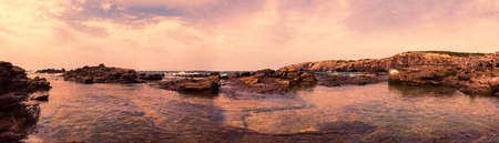 Wilderness seascape at twilight in this suggestive 180 degree Immersive panorama with rock formations carved by wind and clear seas  Archivio Fotografico