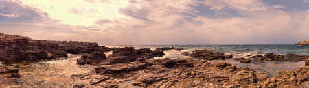 Wilderness seascape at sunset in this suggestive 180 degree Immersive panorama with rock formations carved by wind and rough seas