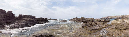 Immersed in the wilderness between rocks sculpted by wind and agitated blu sea with a surreal atmosphere in this huge panoramic 180 degrees view Archivio Fotografico - 132485143