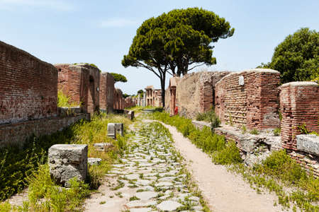 Roman empire village street view and its architecture in archeological excavation of Ostia Antica with cobblestone pathway and tenement and ancient shop ruins, Rome Italy Archivio Fotografico