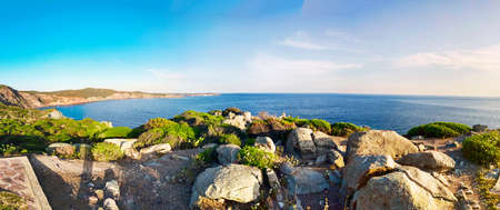 Wonderful immersive 180 degrees picture over the cliff above blue sea water bay in wilderness mediterranean area, ancient gray stones and green bushes with no one at horizon and summer light