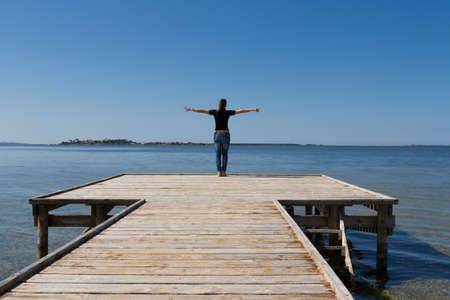 mujer joven con los brazos bien abiertos contra el cielo azul
