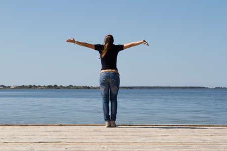 young woman with arms wide open against blue sky photo