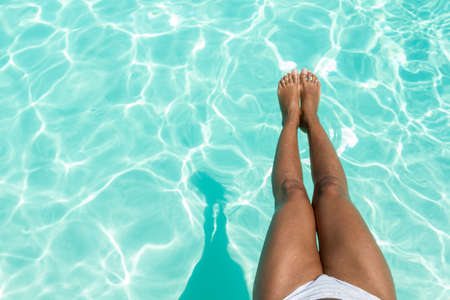 Woman relaxing in a pool - legs close up photo