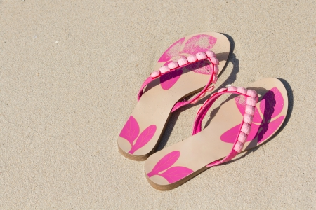 Pink slippers in the sand sea photo
