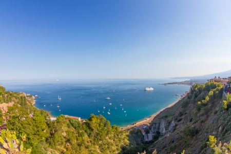 Sicilian seascape from Taormina  mount Etna beyond the blue sea and trees frame on foreground