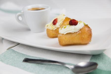 Neapolitan babà and coffee on white white dish Stock Photo