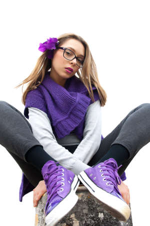 intriguing: Low angle view of a teenage girl sitting cross-legged with nerdy glasses and intriguing expression.
