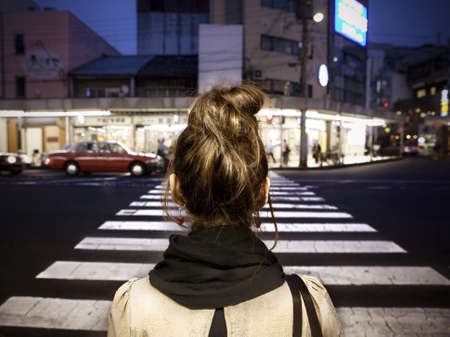 Woman crossing a street at night Stock Photo - 17025001