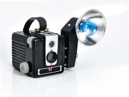 Vintage camera on white background that has a flash accesorie with a blue light photo