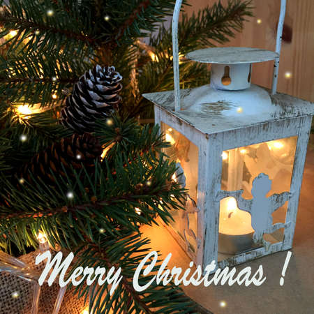 """White decorative lantern-a candle with an angel on the background of fluffy fir branches, illuminated by a Christmas garland. The Inscription """"Merry Christmas!"""" Archivio Fotografico"""