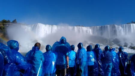 Group of people in ponchos watching Niagara Falls on clear day