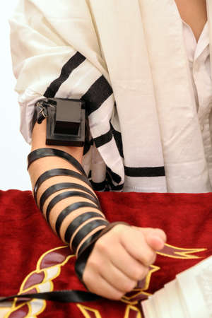 A young man using a Jewish Tefillin on his hand and wearing prayer shawl for praying