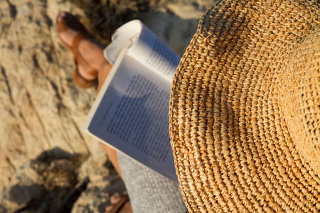woman with straw hat reading a book at vacation