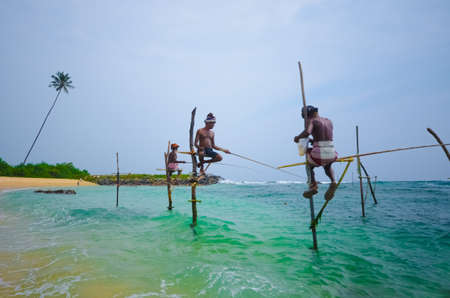 Koggala, Sri Lanka. March 25, 2014 : The local fishermen are fishing in unique style an March 25, 2014 . The standing on the single timber pole and this craft passed down from generation to generation 에디토리얼