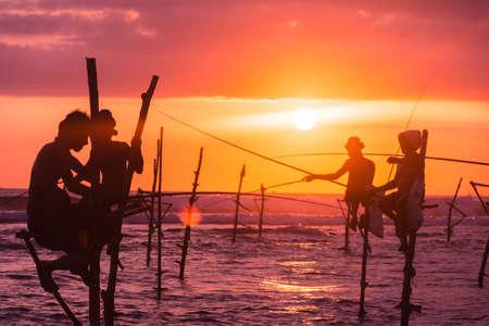 Pescadores de zancos tradicionales en la puesta de sol Sri Lanka Foto de archivo - 59835485