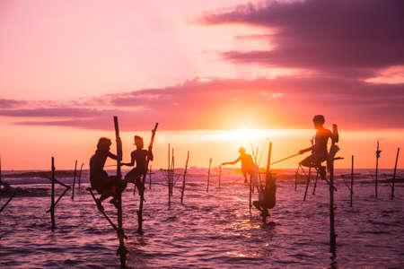 Silhouetten van de traditionele vissers bij de zonsondergang in de buurt van Galle in Sri Lanka.