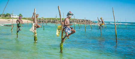 Silhouetten van de traditionele vissers steltenlopers, staande op de single hout paal kan alleen gevonden in deze Indische Oceaan op 24 maart 2013 in Koggala, Sri Lanka.