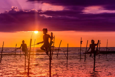galle: Silhouettes of the traditional fishermen at the sunset near Galle in Sri Lanka. Stock Photo