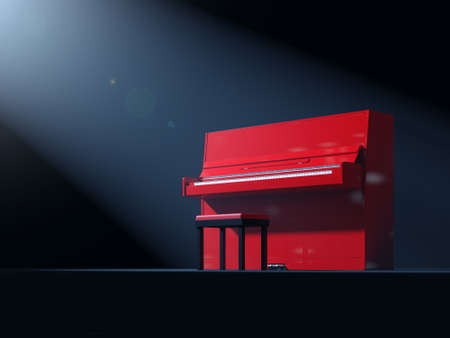 Red classical upright piano with chair on stage illuminated by ray of light photo