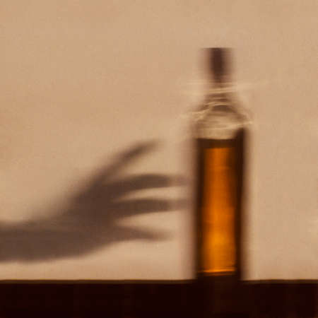 Alcohol addiction concept - shadow of hand reaching for bottle of alcohol