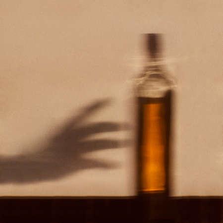 alcoholismo: Alcohol concepto de adicción - sombra de la mano para llegar a la botella de alcohol
