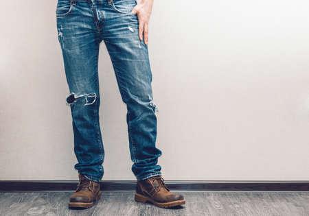 piernas hombre: Las piernas del hombre joven de la manera en pantalones vaqueros y botas en el piso de madera Foto de archivo