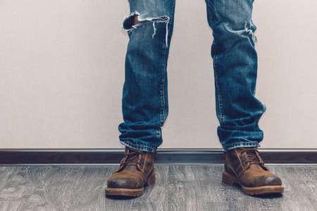 de vaqueros: Las piernas del hombre joven de la manera en pantalones vaqueros y botas en el piso de madera Foto de archivo
