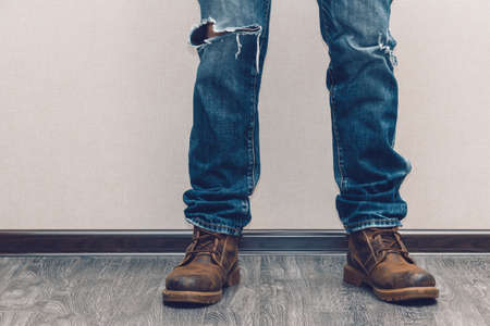 ripping: Young fashion mans legs in jeans and boots on wooden floor