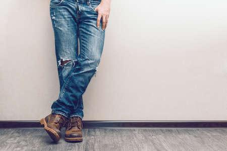 hombre: Las piernas del hombre joven de la manera en pantalones vaqueros y botas en el piso de madera Foto de archivo