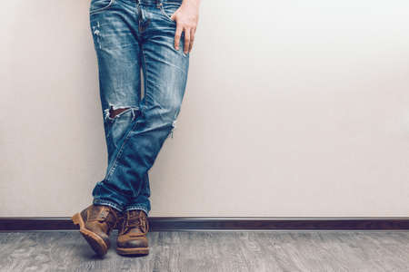 blue denim: Young fashion mans legs in jeans and boots on wooden floor